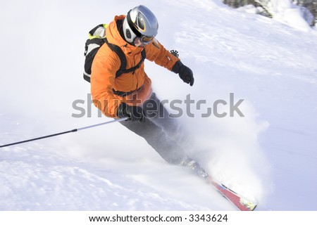 mountain ski rider in orange sharp stop - stock photo