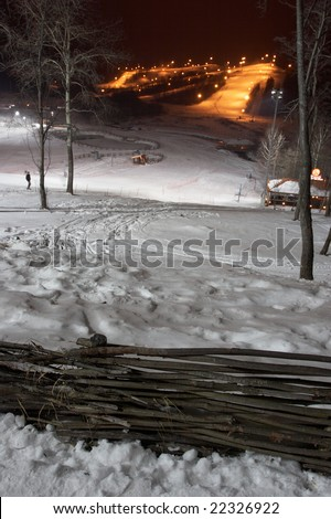 Mountain-skiing slope at night. In the foreground a fence. Small houses-hotels are visible - stock photo