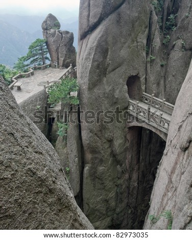 Mountain stone bridge above rocky precipice between the rock. And aerial view at the valley. Huangshan, China, Asia. - stock photo