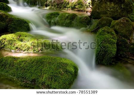 Mountain stream among green stones - stock photo