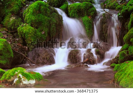 Mountain stream among the mossy stones - stock photo