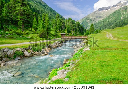 Mountain stream and the high peaks of the Austrian Alps - stock photo