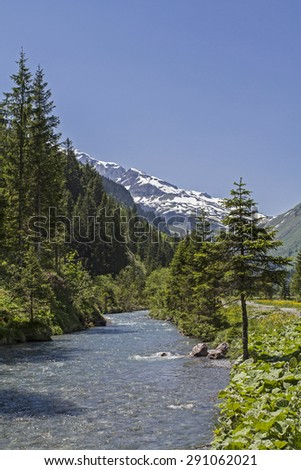 Mountain stream flowing through the Urnerboden, the largest alp in Switzerland - stock photo