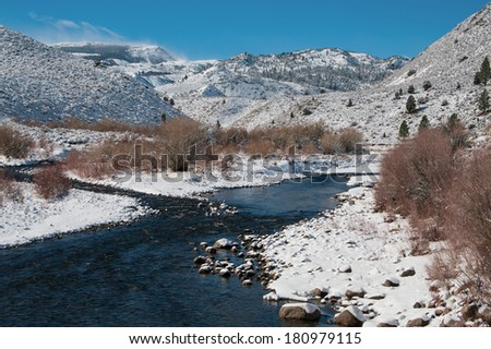 Mountain Stream in Winter:  Water flows through a snowy landscape in the Sierra Nevada Mountains near Yosemite National Park.  - stock photo