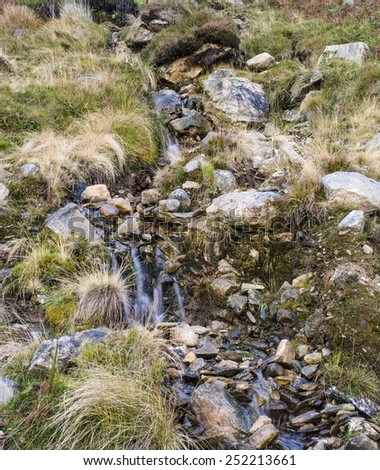Mountain stream, small waterfall through boulders and grass - stock photo