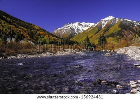 Mountain stream with brilliant fall colored trees changing at the base of snow covered peaks - stock photo