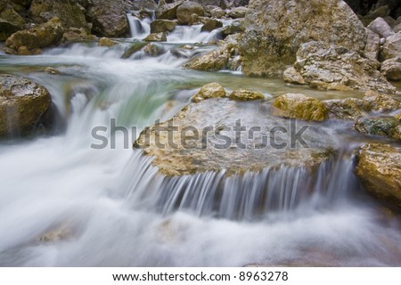 Mountain stream with water flowing over rocks - stock photo