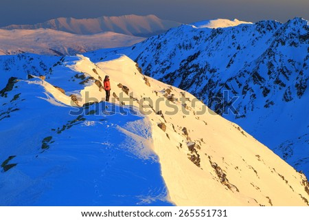 Mountain summit and distant hiker standing and watching the sunset in winter - stock photo
