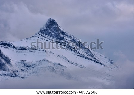 Mountain summit, shrouded in clouds, cold - stock photo