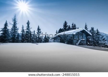Mountain sun over the ski hut in blue - stock photo