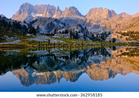 Mountain Sunrise Reflected in Alpine Lake.  The Minarets and Ediza Lake, The Ansel Adams Wilderness, California - stock photo