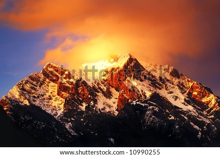 Mountain top covered in clouds at sunset - stock photo