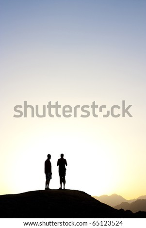 Mountain top in egypt at dusk as the sunsets, 2 people stand silhouetted against the sun - stock photo