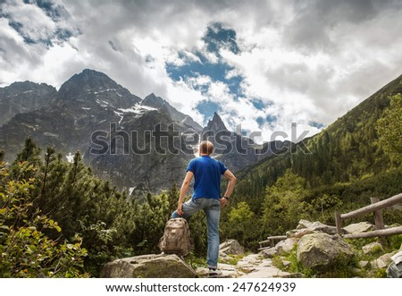 Mountain traveler looks on wild rocks - stock photo