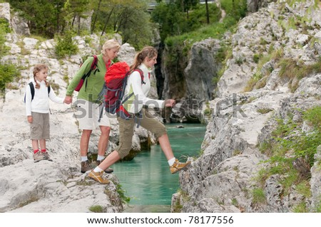Mountain trek - family crossing through river - stock photo