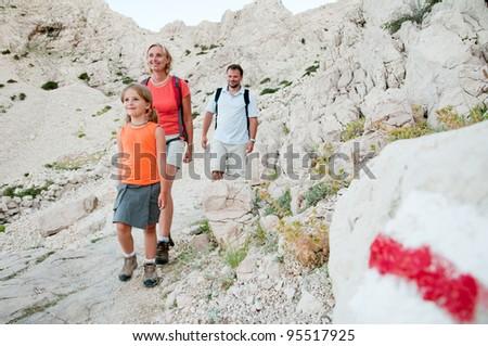 Mountain trek - family trekking on red trail - stock photo