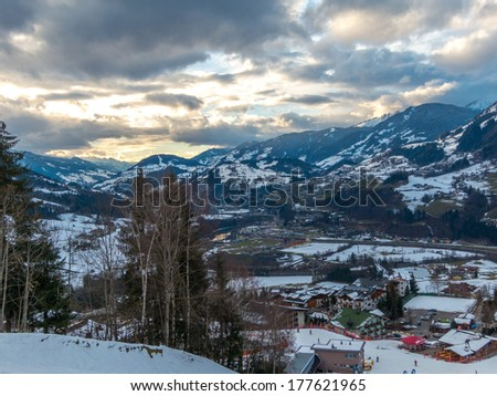 Mountain valley with a small town at winter covered with snow - stock photo