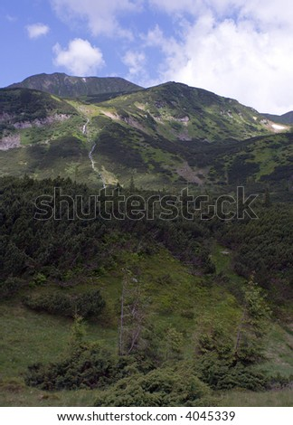 Mountain view with juniper forest and waterfall cascade in the distance - stock photo