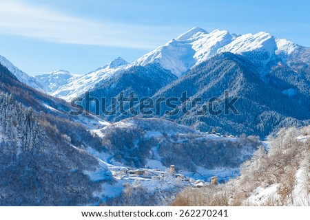 Mountain village on the snowy slope in Caucasus - stock photo