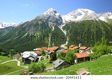 Mountain village with snowy peaks in the background - stock photo