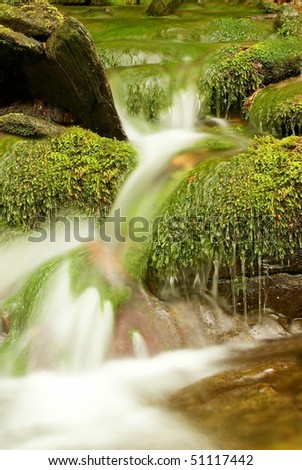 Mountain waterfall flowing between mossy stones in spring forest. - stock photo