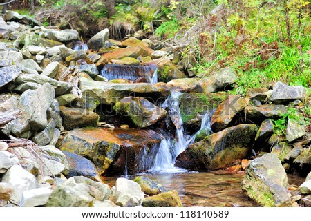 Mountain waterfall in autumn beech forest - stock photo
