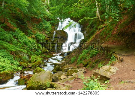 Mountain waterfall in the European mountains in summer