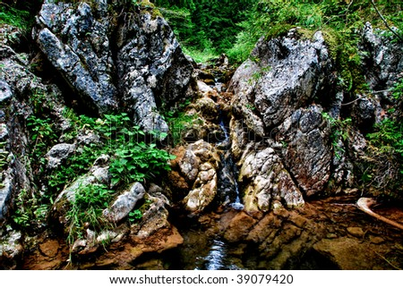 mountain waterfall with green moss and rocks - stock photo