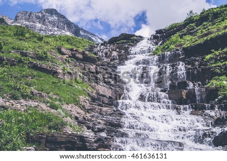 Mountain waterfall with rough cliffs and blue sky