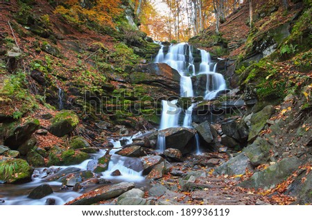 Mountain waterfall with yellow foliage and rocks in autumn forest  - stock photo