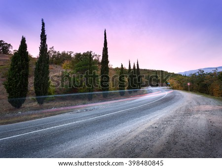 Mountain winding road passing through the forest with blurred car lights in motion with colorful sky at sunset in summer - stock photo
