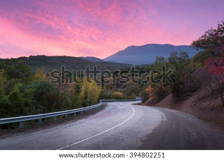 Mountain winding road passing through the forest with dramatic colorful sky and red clouds at sunset in summer - stock photo