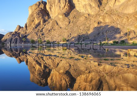 Mountain with reflections in a river, Fint Oasis, Ouarzazate, Morocco. - stock photo