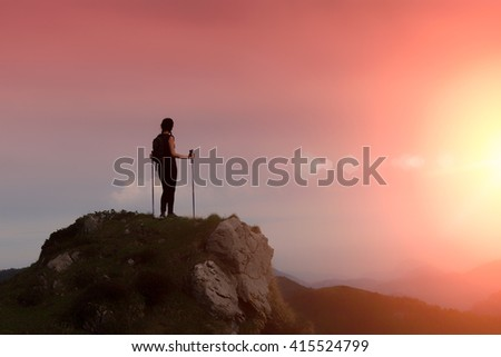 Mountain woman alone in a fiery sky looking at the horizon