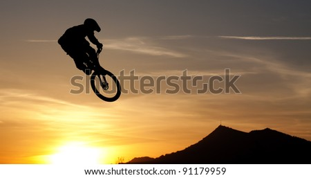Mountainbike Jump against sun and mountain silhouette in back - stock photo