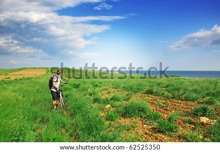 Mountainbiker observing beautiful nature with ocean in background - stock photo