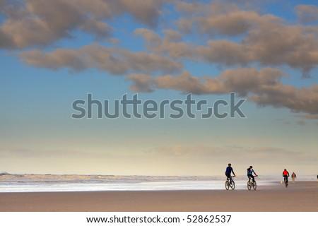 Mountainbikers on the beach - stock photo