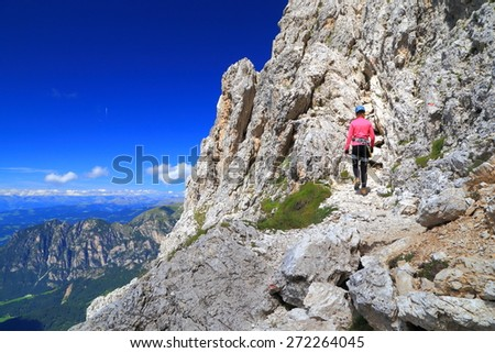 "Mountaineer approaching via ferrata ""Passo Santner"" in sunny day, Catinaccio massif, Dolomite Alps, Italy - stock photo"