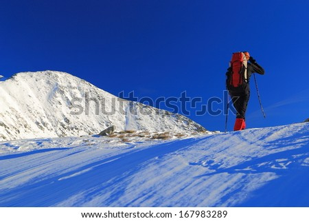 Mountaineer ascending the snowy mountain in winter - stock photo