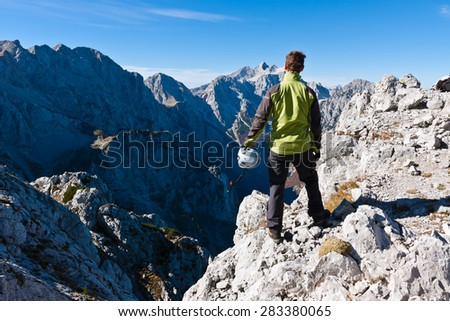 Mountaineer at the top of the Krofi?ka mountain enjoying the view, Slovenia