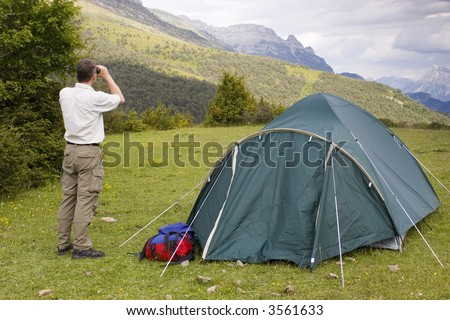 Mountaineer beside his tent looking with binoculars at the bad weather. - stock photo