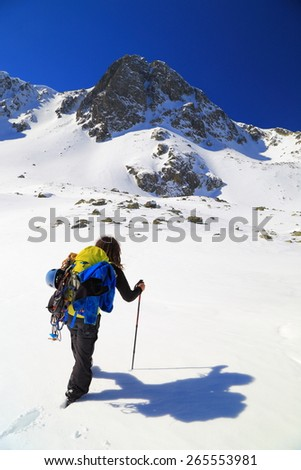 Mountaineer carries heavy backpack while ascending a sunny mountain slope in winter - stock photo