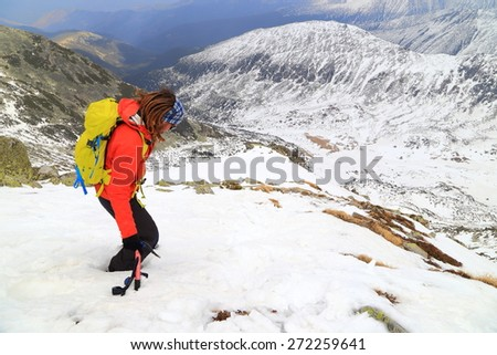 Mountaineer carries yellow backpack on snowy slope in overcast day - stock photo
