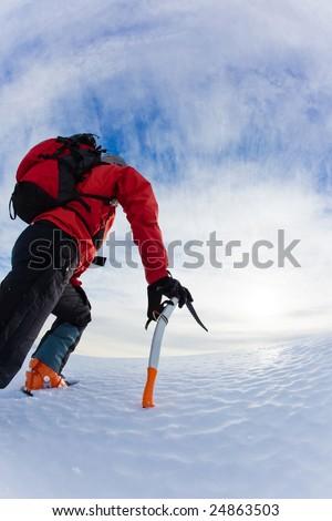 Mountaineer climbing a glacier; vertical frame. - stock photo