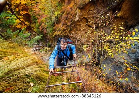 Mountaineer climbing a rusty iron ladder on a mountain - stock photo