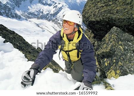 Mountaineer climbing a steep slope - stock photo
