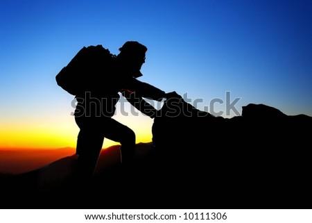 Mountaineer climbing at sundown - stock photo