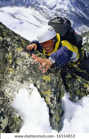 Mountaineer climbing snowy rock face - stock photo