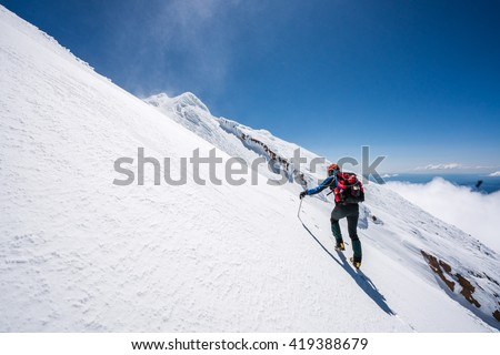 Mountaineer climbs snowfield on a sunny day high on a mountain. - stock photo