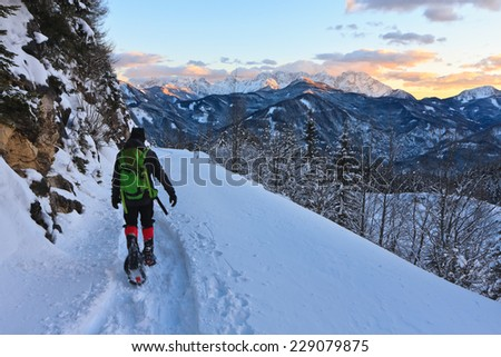 Mountaineer descending from a mountain with  the view of the setting sun over the snowy Kamnik-Savinja Alps while descending from a mountain in the winter evening, Austria - stock photo